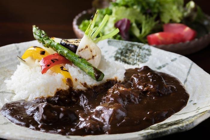 """スパイスと牛肉、野菜のうま味が溶け込んだ""""黒カレー""""は人気の一品。季節の信州野菜のグリルが添えられていて、見た目も鮮やか♪サラダ付きです。"""