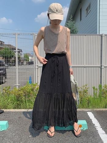 ナチュラルな風合いのスカートは、黒でも涼し気に着こなせます。丈が長いので、足元はビーサンでしっかり肌を見せているのがポイントです。