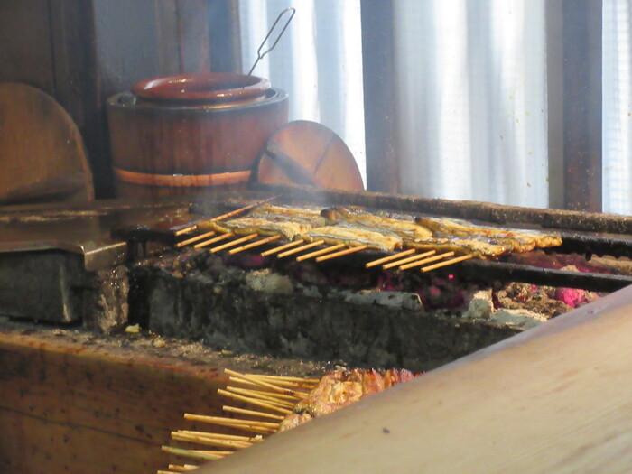 焼き場では、うなぎが次々と焼かれています。使い込まれた焼き台やうちわに歴史を感じますね。焼く様子を間近で見られるカウンター席もおすすめ。