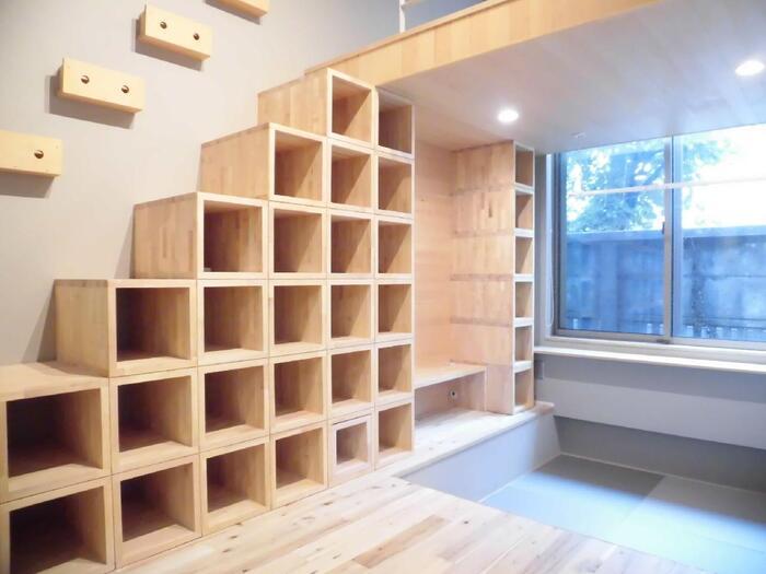 階段下を上手に使った圧巻の造作本棚。格子状のオープン棚は、本棚としてはもちろん雑貨のディスプレイコーナーとしても使えます。ボックス型の収納アイテムをプラスすれば、細々としたものの収納もおまかせ。フレキシブルに使えるマルチ収納として活躍しそう。