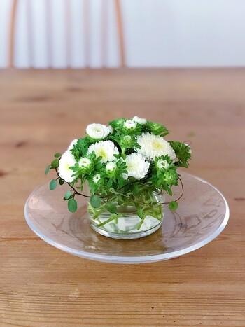 小さなグラスに花を生けています。ガラス皿を敷くことでよりラグジュアリーな雰囲気に。低めに生けることで、どこから見ても美しく魅力的に飾ることができます。