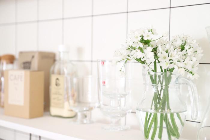 白い小さな花をガラスのピッチャーにざっくりと。花瓶がなくても、透明感のあるグラスやピッチャーなどで代用するのも良いですね。家にあるものを使えば、気負いなく花を取り入れることができます。