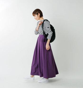 濃いパープルのロングスカートに、ボーダートップスをタックインしたコーディネート。ボーダー×ロングスカートの組み合わせは定番ですが、パープルをチョイスするだけでおしゃれ度がグッと高まります。