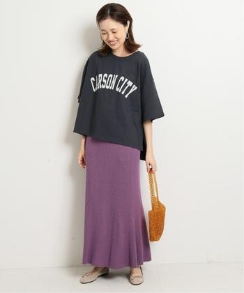 パープルのニットスカートに、ネイビーのゆるTシャツを合わせたコーディネート。あえてタックインせずに裾を出すことで、大人のゆとりを感じさせるこなれコーデに仕上げています。