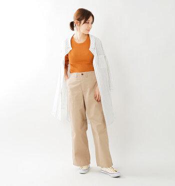 ベージュのワイドパンツに、オレンジのトップスをタックイン。ストライプ柄のシャツワンピースを羽織って、Iラインを意識したスタイルアップコーデの完成です。足元はあえてスニーカーで、上手にカジュアルダウンしているのがポイント。