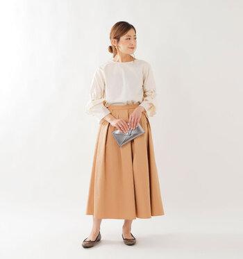 ベージュのフレアスカートに、ベージュのブラウスをタックインしたワントーンコーデ。上品でフェミニンな着こなしは、クラッチバッグをプラスしてちょっとしたお呼ばれスタイルにもぴったりです。