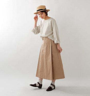 ベージュのロングスカートに、薄いベージュのトップスを前だけタックイン。足元は靴下とストラップサンダルの組み合わせで、トレンド感たっぷりに仕上げています。ナチュラル素材のハットは、季節の変わり目コーデにもぴったり。