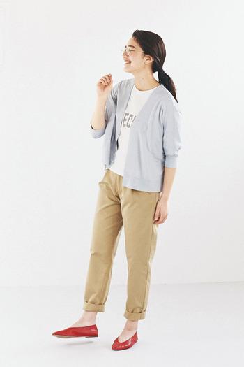 ベージュのパンツは裾をロールアップして、程よい抜け感をアピール。白のTシャツにカーディガンを羽織ったラフスタイルを、赤のパンプスでレディライクに格上げしています。