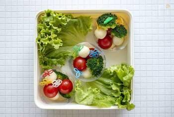 大勢で食べることが多くなる運動会のお弁当は、まず余白を目立たせないよう対角線上にレタスを敷きます。その上にブロッコリーやトマトなどをピンチョスにしたアイテムをプラスチックのカップなどに入れ並べていきます。