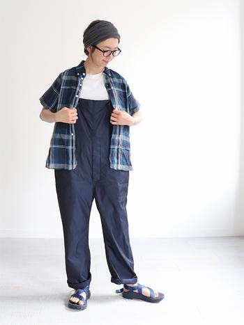 ネイビーのオーバーオールに、チェック柄の半袖シャツを合わせた春夏にぴったりなコーディネートです。インナーは白トップスで、チェック柄を邪魔しないシンプルなものをチョイス。足元はオーバーオールと色を合わせたブルーのサンダルで、全体的に統一感のある着こなしに仕上げています。