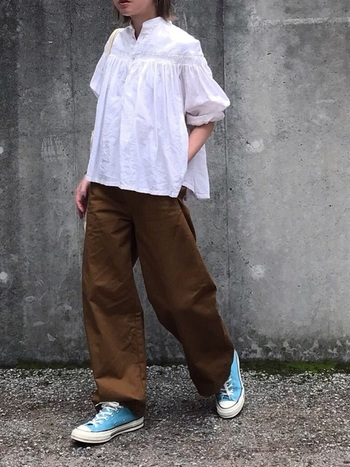フェミニンなデザインの白ブラウスは、メンズライクなブラウンパンツと合わせて甘辛MIXコーデにすると、ひとつ上の着こなしに。スニーカーの差し色が、大人の遊び心を感じさせますね。