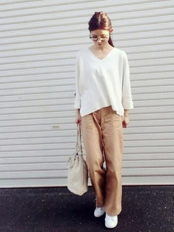 ワイドシルエットのベージュカーゴパンツに、白のゆったりトップスを合わせたコーディネート。深めのVネックが、カジュアルなボトムスにフェミニンな印象を与えてくれます。スニーカーも白で合わせて、まとまり感のある着こなしに。