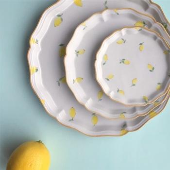 昨年から、彫りではなく、絵付けによる『レモン』シリーズの器が登場しています。白地にレモンの黄色が映えて、初夏の爽やかさを感じさせるデザインです。  柔らかなタッチで描かれたレモン柄は、食卓に並べるだけで、華やかさを演出してくれます。  こちらは、レモン総柄のお皿。パンケーキやアイスクリームなど、デザートを盛り付けるのにもぴったりです。
