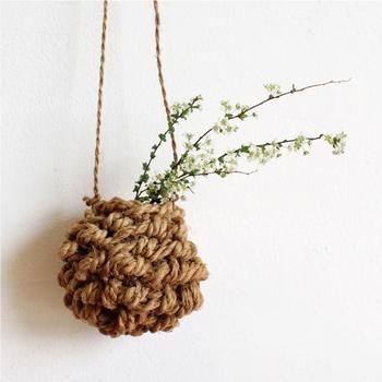 """シナの木の皮の繊維で縄を作り、指編みでざっくりと編まれた""""花かご""""。いかにも手作りらしい素朴さがあり、可憐な花をそっと引き立ててくれます。"""