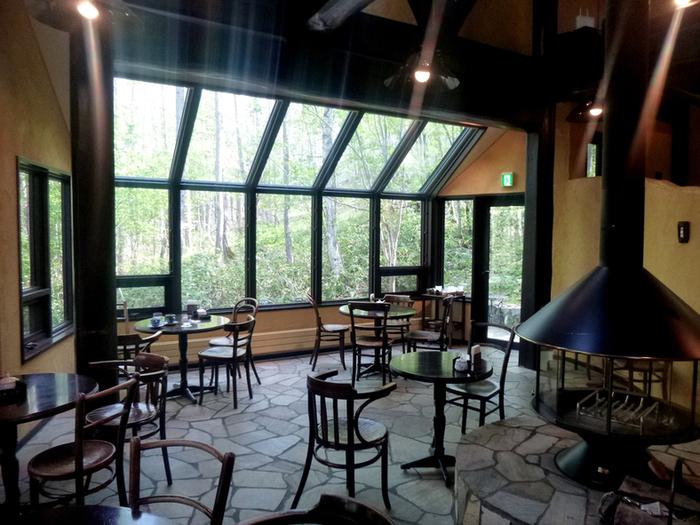 店内に入ると、ほっと息をつける素敵な空間が広がっています。天井近くまで大きく取られた窓からは、たくさんの光と森の風景が飛び込んできます。インテリアも丸みを帯びたテーブルや椅子が優しい雰囲気で、この場所にぴったり。