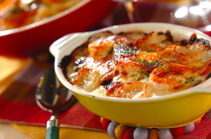バターライスにゆるめに仕上げたホワイトソースをたっぷりかけて。ピザ用チーズをかけたら、焦げ目がつくまでしっかりと焼き上げると食欲をそそる見栄えの良いドリアの完成です。