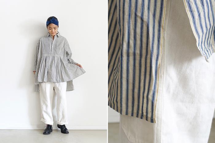 """ヴィンテージ薫るデザインのプルオーバーシャツは、サイドのスリット部分に「耳」が来るように。味わい深いストライプ生地は、まるで""""大切に受け継がれてきた服""""のような佇まいです。胸下で寄せたギャザーや、前後で長短をつけた裾が躍動感のあるシルエットを作り出します。"""