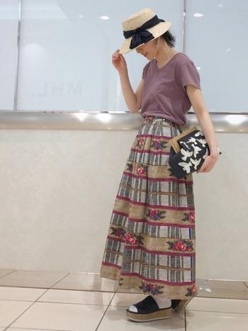 花柄のロングスカートと合わせて、かわいく着こなしたコーデ。帽子やバッグ、靴の黒が全体のコーデを引き締めてくれています。