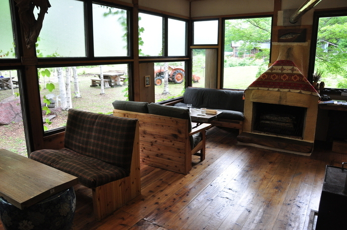 中に入ると、たくさんの窓から光が差し込む明るい空間が広がります。ソファ席もあり、ゆったり過ごすにはぴったり。可愛らしい薪ストーブがあり、冬でも温かく過ごせます。