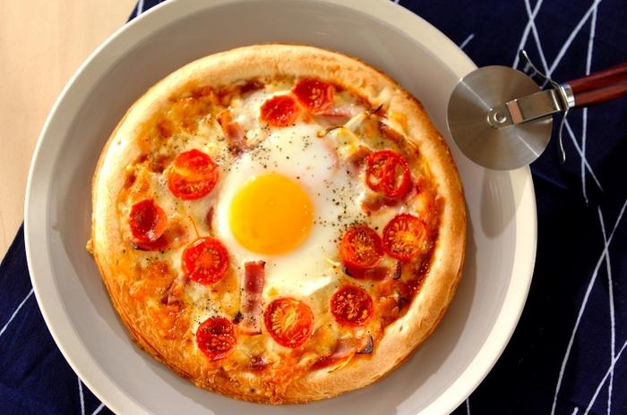 テーブルを華やかに彩る、卵が真ん中にどーんとのった豪快なお月見ピザ。火加減を調節して、卵はお好みの固さにして。