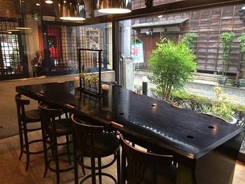 陶器店の一角にあり、シックな内装がステキです。黒塗りのハイテーブルには、底がとがったグラスが置けるように穴を作るなどのこだわりも。