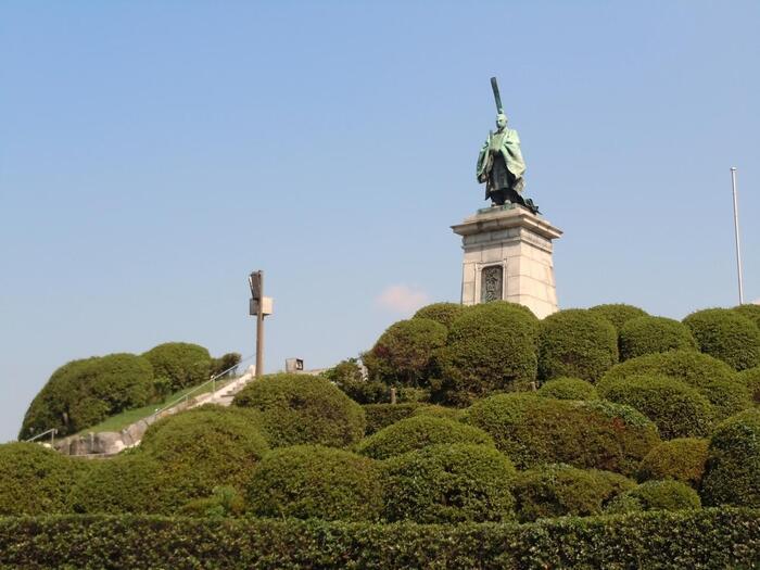 福岡県庁の目の前に広がる東公園は、1周が約760mありウォーキングやお散歩スポットとしても人気。元寇襲来の際に活躍したと言われる「亀山上皇」銅像が、東公園のシンボルとして都会のオアシスを見守っています。周りを取り囲むツツジは、春には満開となりより華やかな公園を彩ります。