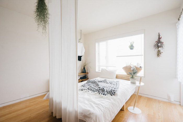 ワンルームでは、どうしてもベッドが丸見えになってしまいがち。天井から布を吊るすことで、寝る空間とリビングスペースを仕切りつつ目隠しをしています。光を通すカーテンを選んだり両サイドを開けておくことで、リビングスペースにも光が通るようになっているのがポイントです。