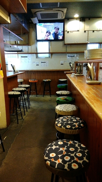 大阪・肥後橋にあるパスタやカレーがおいしい居酒屋。店内はカウンターになっていて、マリメッコのファブリックがかわいい椅子が並べられています。