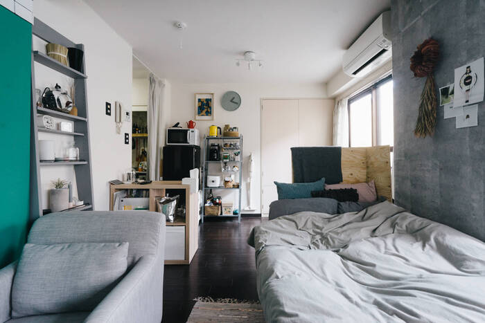 縦長の部屋にベッドとソファを並べて置いた、珍しい配置。それぞれの家具を入口と反対方向に向けつつ、手前に家具を置いたり、板で目隠しすることで、キッチン側からもリビング側からもスペースを区切る工夫がされています。