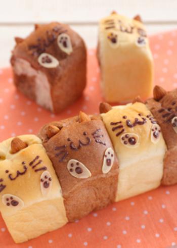 スリムタイプの食パン型を使って焼くちぎりパンのレシピ。アーモンドで付けたネコの耳と手がかわいさのポイント。中にはカスタードクリームが入っているので子供に喜ばれそうです。