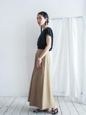 ロング丈のフレアスカートはきれいめな印象なので、プリントTシャツをラフに合わせてバランスをとりましょう。靴は楽なフラットサンダルで、抜け感を出して。