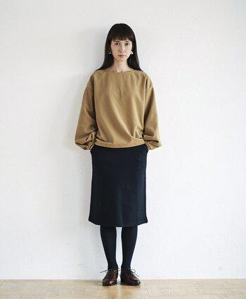 黒のタイトスカートに、ベージュのトップスを合わせたシンプルなコーディネート。タイツとシューズもダークトーンで色を合わせて、美脚見え効果も期待できる着こなしです。