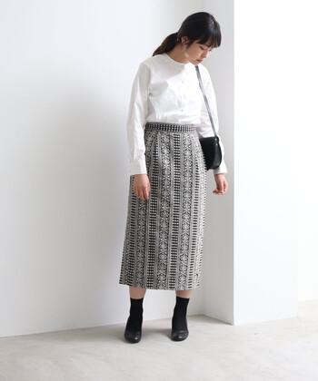 アンティーク調の刺繍柄を施した、シックな印象のタイトスカート。トップスは白ブラウスを合わせて、上品にまとめています。靴とバッグは黒で揃えて、強めの引き締めカラーをプラス。ジャケットなどを羽織れば、さらにきちんと感のあるスタイリングにクラスアップできます。