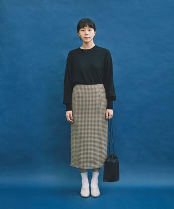 チェック柄のタイトスカートは、秋冬コーデに大活躍してくれるアイテム。黒のトップスをきっちりとタックインして、上品な雰囲気で着こなしています。足元はあえて白でまとめて、抜け感のあるワンポイントに。