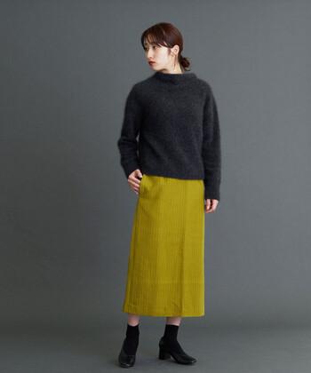 明るめカーキカラーのタイトスカートに、黒のトップスを合わせたコーディネート。足元も黒で揃えて、合わせるカラーに悩んでしまいがちなスカートを、シックに着こなしています。アウターをプラスすれば冬までOKのコーディネートに。