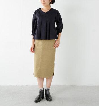 ベージュのタイトスカートに、ネイビーのトップスを合わせたコーディネート。短め丈のトップスを選べば、タックインしなくてもバランスのよいスタイリングが叶います。黒のショートブーツで、季節感をアピール♪