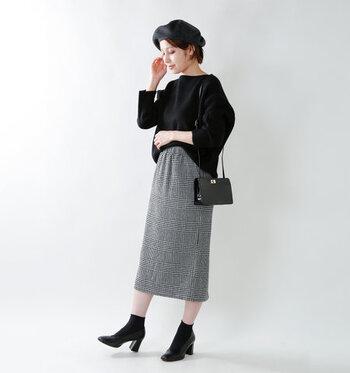 タータンチェック柄のタイトスカートは、大人っぽさを手軽に演出できるデザイン。黒のゆったりトップスをフロントタックインして、カジュアルシックに仕上げています。小物はすべて黒で揃えて、デイリーに使えるモノトーンコーデに。
