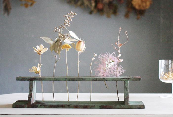 試験管ホルダーを花器として活用しています。一本ずつ違った種類のドライフラワーをアレンジすることで、まるで可愛いお花の実験をしているような風情を作り出しています。