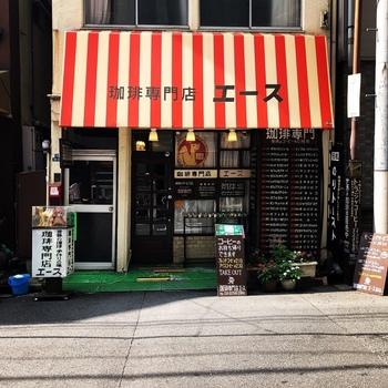 神田駅から徒歩3分、クラシカルな紅白ストライプの日差しが目を引く「珈琲専門店 エース」。お店の右手には世界のコーヒーの産地がずらりと書かれています。神田を訪れる人たちの憩いの場として親しまれている純喫茶です。