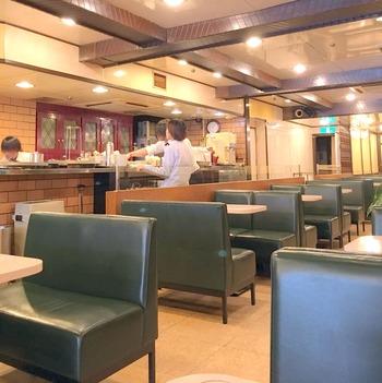 奥行きのある店内は100席と広く、アイボリーのテーブルと深緑色のソファーがずらりと並びます。テキパキとしたスタッフの接客も素晴らしく、時間を忘れてくつろげる雰囲気です。
