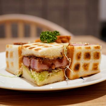 """「ペリカンカフェ」の""""ハムカツサンド""""は、炭火で両面を焼いたパンに厚切りのハムカツと千切りキャベツを挟んだサンドイッチ。地元ブランドの「浅草ハム」とマスタードのきいた自家製マヨネーズの相性が抜群です。"""
