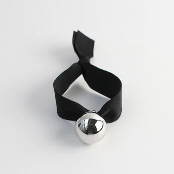 黒のリボンにシルバーのボールモチーフがついたブレスレット。リボンの柔らかさが、モノトーンのクールな印象を和らげてくれます。