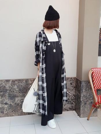 黒×白のチェックが印象的なシャツワンピをコートのように羽織って。黒のサロペットのインナーに白Tシャツを着れば、モノトーンコーデが完成します。