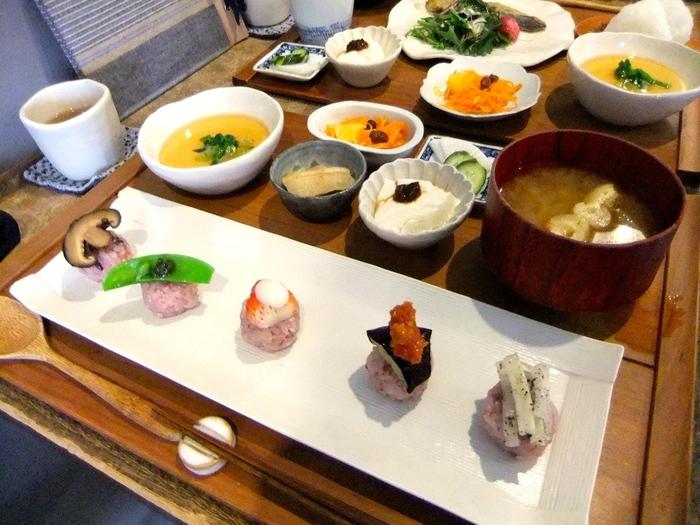 """旬の野菜を使った「にぎり野菜寿司膳」は、ちょこんと小さな野菜のお寿司と小鉢、汁物のセット。また、おむすびと季節ごとに変わる献立で構成された「むすび膳」も。どちらも古くから日本に伝わってきた""""手のひらには巧妙なる力が宿っている""""という思いが込められているんだそう。"""