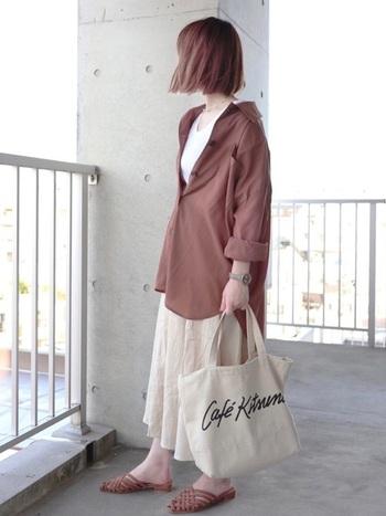 白Tシャツに白スカートの夏カラーなコーデも、ブラウンのビッグシャツを羽織るだけで、一気に秋コーデに。Tシャツ×シャツは、秋口に試したいテクニックのひとつですね。