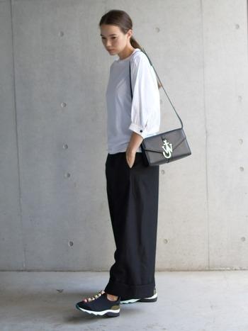 白のトップスに黒のボトムの究極シンプルコーデに、レディーな印象のかっちりバッグを合わせて。足元がスニーカーなので、程よい抜け感もあります。