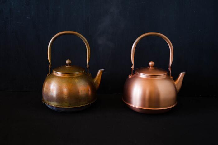 """こちらは日本の伝統技術を活かした上質なプロダクトを提案するブランド、「東屋(あづまや)」の銅のやかんです。塩素を分解する優れた作用を持つ銅は、お湯を沸かす「薬缶」にも最適な素材です。使うほどにだんだんと美しい飴色へと変化していくので、""""育てる""""楽しさを味わいながら長く使い続けることができます。(右が新品のやかん、左が一年使用したやかんです。)"""