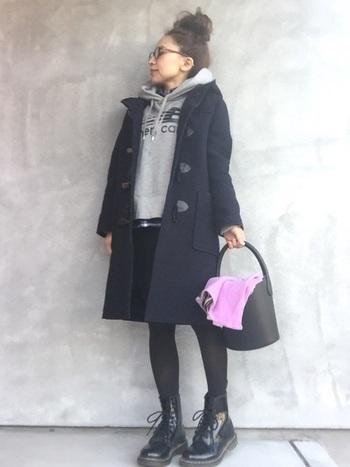 紺色のダッフルコートにグレーのロゴパーカを合わせたスタイリング。コートと同じ丈感のスカートでコンパクトにまとめて。ボリューム感のあるブーツで、上下のバランスを上手く取っています。