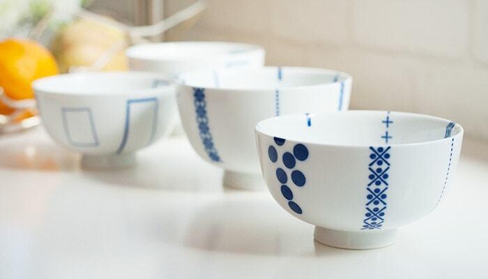 """長崎県の伝統工芸として有名な『波佐見焼』は、なめらかな白磁に呉須で絵付けをした上品なデザインが特徴です。こちらは日本の伝統技術を活かしたおしゃれなプロダクトを提案するブランド、「東屋(あづまや)」が手掛けた波佐見焼のご飯茶碗です。伝統手法の""""印判(転写シートで絵柄を焼き付ける方法)""""を用いてつくられた「花茶碗」は、丸みのある愛らしいフォルムとモダンな柄が魅力的です。"""