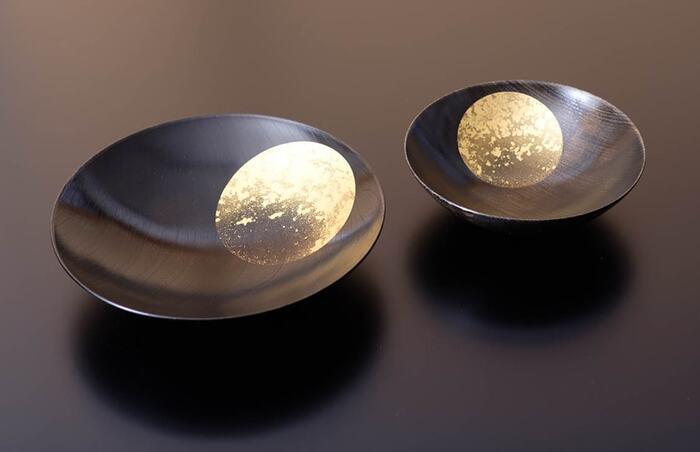 こちらは石川県・金沢市の金箔工芸ブランド、「箔一(はくいち)」の高級漆器「おぼろ月」のボウル(深皿)です。天然木の美しい木目を活かした木地に、金箔の満月を浮かべた上品なデザインが印象的。見ているだけで華やかな気持ちにさせてくれるおぼろ月は、普段使いはもちろんのこと、お正月やお祝いの席など幅広いシチュエーションに活躍してくれます。